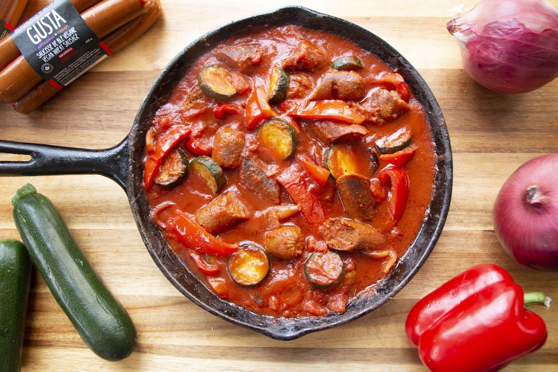 Dans une poêle, faire revenir les saucisses dans l'huile 5 minutes. Retirer les saucisses de la poêle, couper les saucisses en biseau et réserver. Dans la même poêle, faire revenir le poivron rouge, l'oignon et la courgette, à feu vif de 5 à 10 minutes en ajoutant de l'huile au besoin. Ajouter le cumin, le thym, la pâte de tomate, le sirop d'érable, les tomates en dés, le bouillon de légumes, piment rouge broyé (facultatif) et bien mélanger. Saler et poivrer, réduire le feu et laisser mijoter 15 minutes en mélangeant fréquemment. Servir avec du riz basmati.